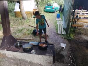Služba připravuje večeři - bramborovou kaši s párky.